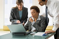 Multi_ethnic businesspeople looking at laptop