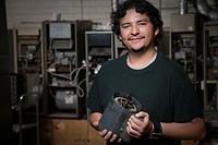 Hispanic refrigeration technician holding part