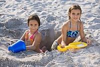 Hispanic girls digging in sand
