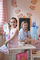 Portrait of two girls holding cardboard cones and smiling on table