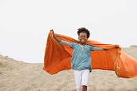 Mixed race girl playing with blanket at beach
