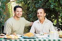 Hispanic men eating outdoors