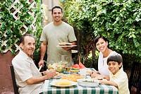 Multi_generational Hispanic family eating on patio