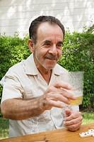 Hispanic man enjoying beer and dominos