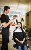 Male hair stylist cutting woman´s hair