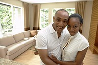 African couple hugging and smiling in livingroom