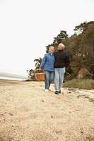 Senior Asian couple walking on beach with picnic basket