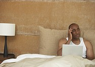 African man using laptop in bed