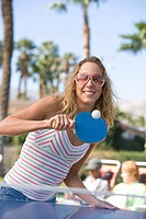 Young woman playing table tennis portrait