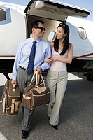 Mid_adult Asian business couple walking in front of private airplane.