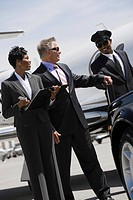 Mid_adult businesswoman senior businessman and chauffeur in front of car.