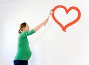 Pregnant woman painting nursery