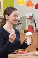 Young woman with latte, laughing