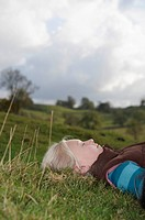 Girl lying on grass looking at sky