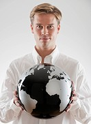 Businessman holding black and white globe