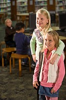 Two elementary school girls smiling in library