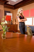 Portrait of young stylish businesswoman in modern office, arms folded