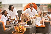 Portrait of family and friends lounging poolside on rooftop terrace in the city
