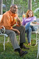 Portrait of African American couple sitting outside with orange juice