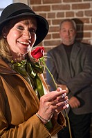 Portrait of mature woman holding red rose, man in background