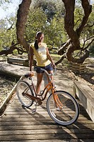 Portrait of young African American woman with bicycle in park