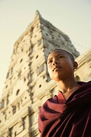 Low angle view of a monk day dreaming in front of a temple, Mahabodhi Temple, Bodhgaya, Gaya, Bihar, India