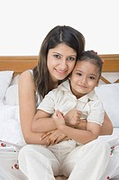 Mother smiling with her daughter on the bed