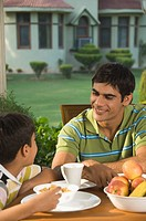 Boy having breakfast with his father and smiling, New Delhi, India