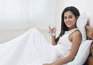 Woman holding a glass of water on the bed, Gurgaon, Haryana, India