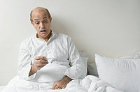 Man sitting on the bed and checking his temperature