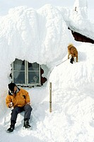 Man and dog in front of a snowed in mountain hut, Areskutan, Are, Sweden