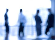 Business people standing and discussing in the office together, blurred motion