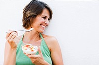 Woman eating muesli with fruit