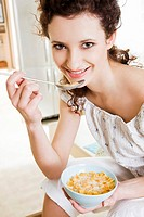 Young woman eating cornflakes with milk