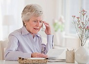 Senior woman paying bills and talking on phone