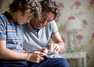 Father and son using cell phone together