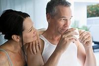 Woman watching husband drink coffee