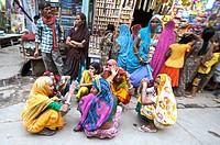 India, Vrindavan, a group of married women kneeling in the street