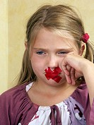 Young girl with glue strip on mouth, lips are sealed