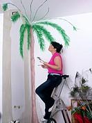 Woman painting palm at wall, ladder, renovating