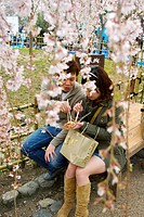 A young Japanese couple sitting on a bench eating some food with chop sticks while surrounded by hanging branches filled with pink cherry blossoms in ...