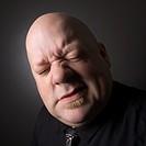 Bald man squinting and making facial expression