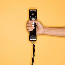 Close up of woman holding telephone receiver on yellow background