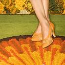 Close-up of female feet wearing orange shoes against colorful retro rug.