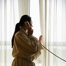 Woman in bathrobe talking on phone and looking out window