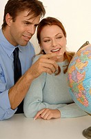 Portrait of a couple looking at a globe together.