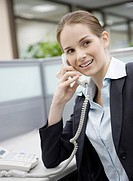 Close_up of businesswoman holding landing phone in the office and looking away