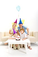 One boy blowing candles with family on his birthday, portrait