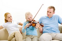 Parents looking at daughter playing violin , portrait