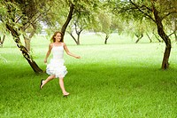 Young woman running on grass